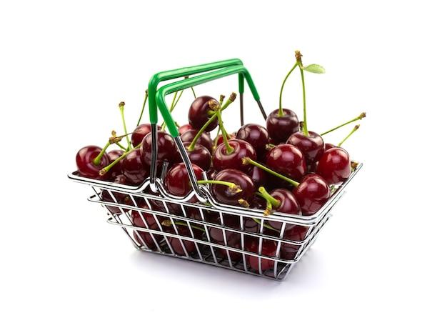 Wiśnia w małym metalowym koszu na białym tle. jedzenie, jagody, zakupy w sklepie, supermarketach.