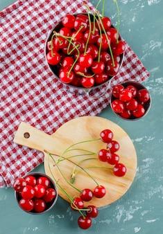 Wiśnia w wiadrach z deską do krojenia płasko ułożona na tynku i ręczniku kuchennym