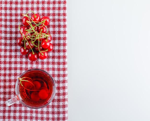 Wiśnia z herbatą leżała na białym i kuchennym ręczniku