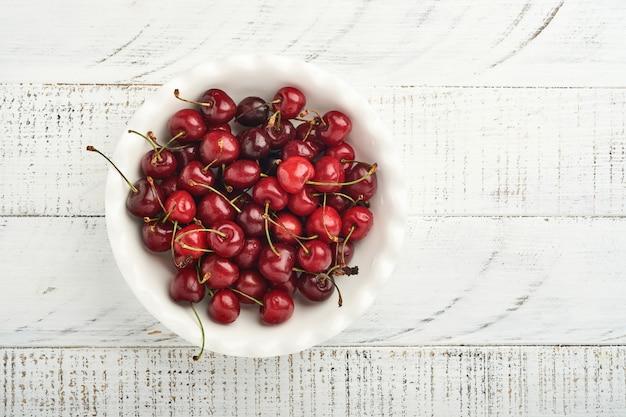 Wiśnia z kroplami wody na białej misce na białym kamiennym stole. świeże dojrzałe wiśnie. słodkie czerwone wiśnie. widok z góry. styl rustykalny. tło owocowe