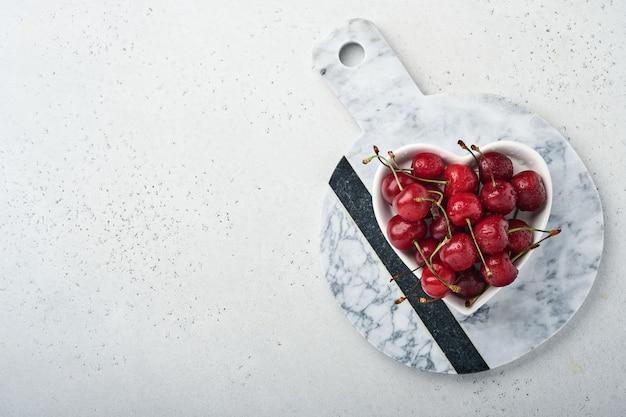 Wiśnia z kroplami wody na talerzu w kształcie serca na białym kamiennym stole. świeże dojrzałe wiśnie. słodkie czerwone wiśnie. widok z góry. styl rustykalny. tło owocowe