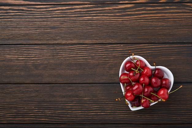 Wiśnia z kroplami wody na talerzu w kształcie serca na ciemnobrązowym kamiennym stole. świeże dojrzałe wiśnie. słodkie czerwone wiśnie. widok z góry. styl rustykalny. tło owocowe