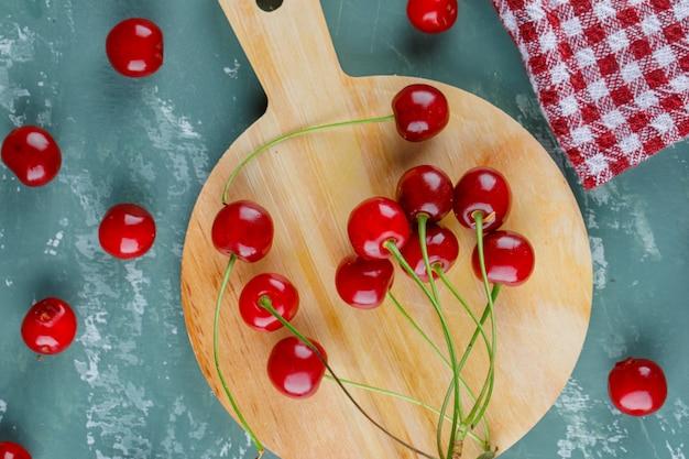 Wiśnia z ręcznikiem kuchennym leży płasko na tynku i desce do krojenia