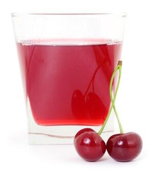 Wiśnie i kieliszek soku wiśniowego na białym tle