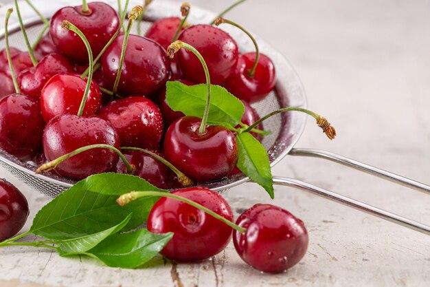 Wiśnie na brązowym drewnianym stole czerwone jagody z zielonymi liśćmi w durszlaku studio strzał kopia przestrzeń