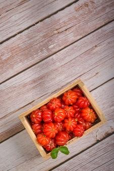 Wiśnie surinam w małym drewnianym pudełku na drewnianej powierzchni