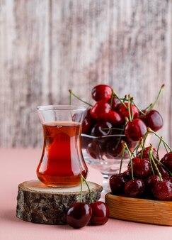 Wiśnie w drewniany talerz i wazon ze szklanką herbaty na desce
