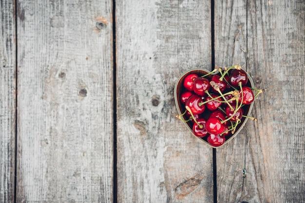 Wiśnie w misce w kształcie serca na rustykalnej drewnianej powierzchni
