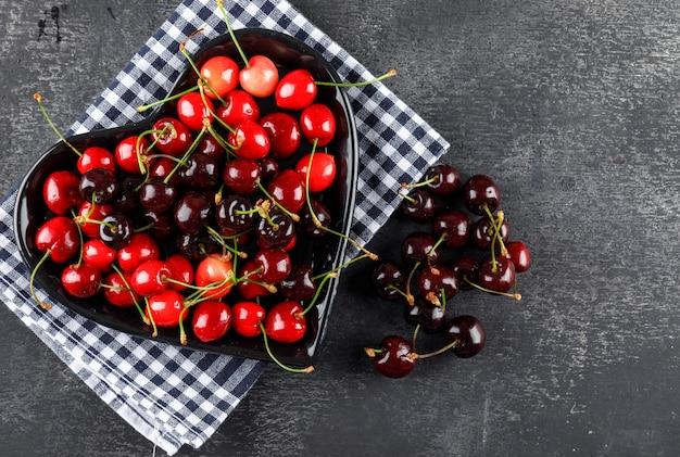 Wiśnie w płaskim talerzu leżały na materiale piknikowym i szarej powierzchni