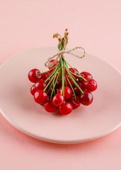 Wiśnie w talerzu na różowym stole. widok pod dużym kątem.