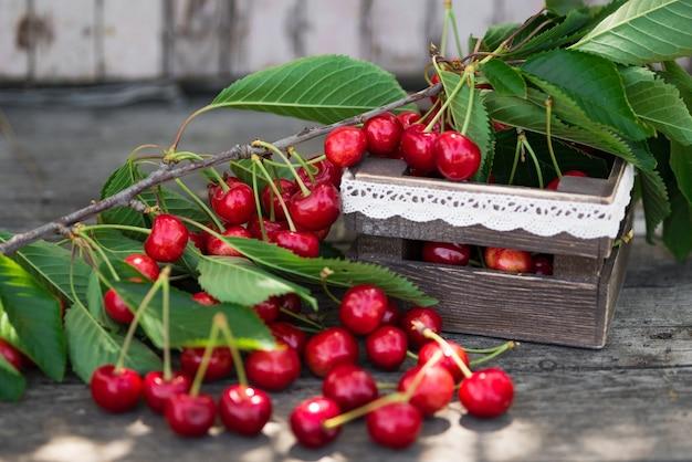 Wiśnie z liśćmi w vintage drewnianym pudełku na rustykalnym drewnianym stole. skopiuj miejsce.