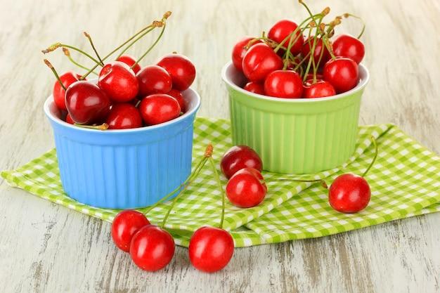 Wiśniowe jagody w miskach na drewnianym stole z bliska