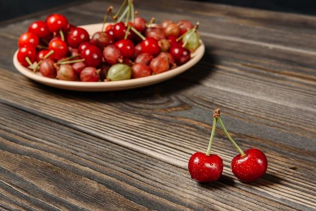 Wiśniowe jagody zbliżenie z selektywnym naciskiem na drewnianym stole. koncepcja zbioru jagód lato.