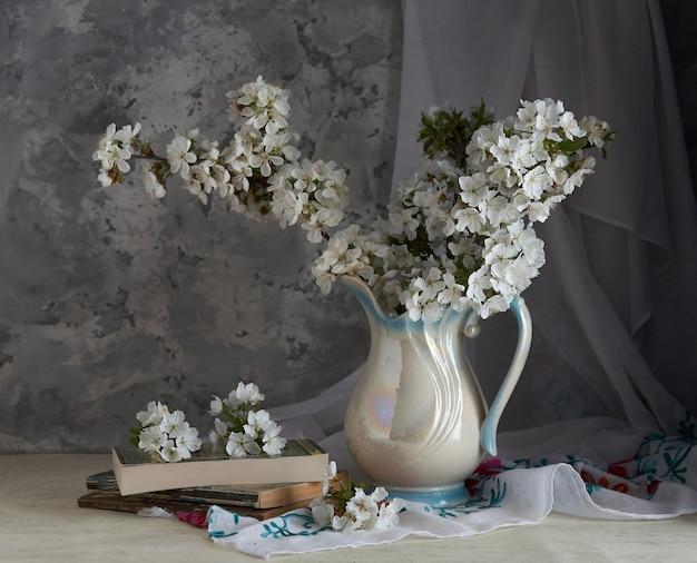 Wiśniowe kwiaty w białym wazonie na szarym tle.