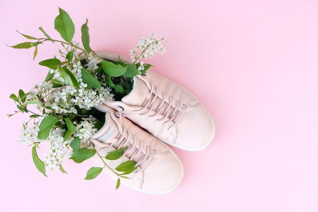 Wiśniowe kwiaty w różowe trampki na różowym tle.