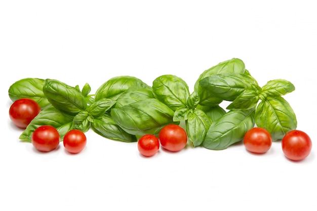 Wiśniowe pomidory i liście bazylii na na białym tle. skopiuj miejsce.