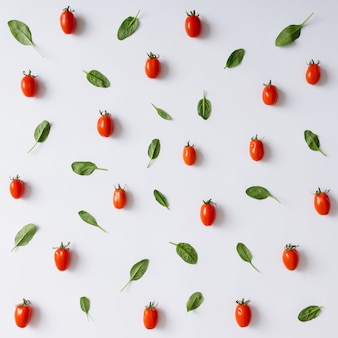 Wiśniowe pomidory i liście bazylii wzór na białej ścianie. leżał na płasko.