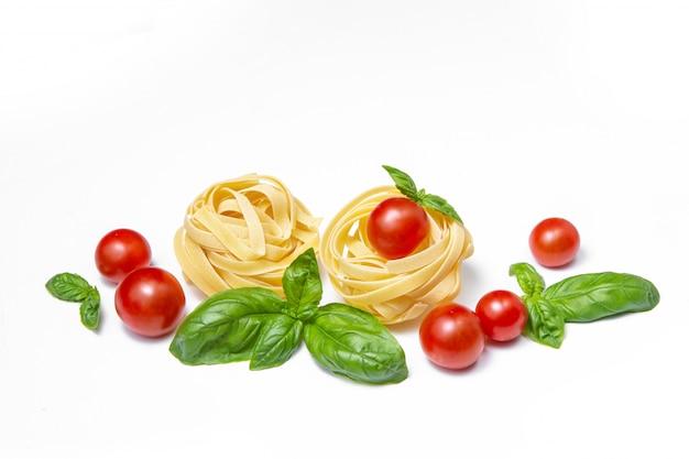 Wiśniowe pomidory, makaron i liście bazylii na białym tle odizolowane. skopiuj miejsce.