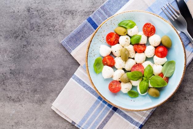Wiśniowe pomidory, mozzarella i zioła na talerzu