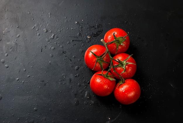 Wiśniowe pomidory na gałęzi, liści szpinaku i przyprawy