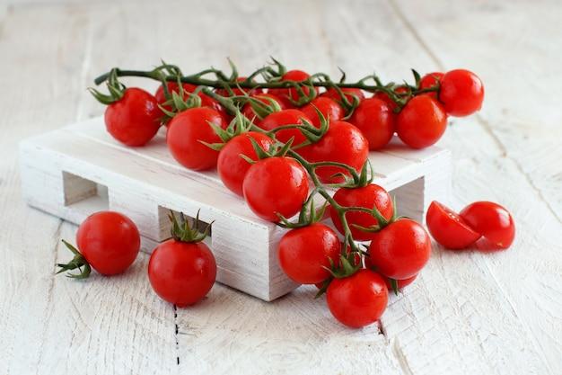Wiśniowe pomidory na starym drewnianym stole z bliska