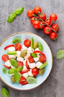 Wiśniowe pomidory, ser mozzarella, bazylia i przyprawy na szarej tablicy łupkowej. składniki sałatki włoskiej tradycyjnej caprese. jedzenie środziemnomorskie.