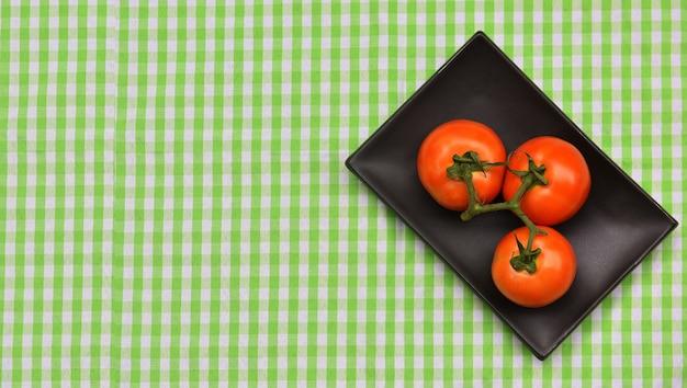 Wiśniowe pomidory umieścić na czarnej płycie tło zielony obrus żywności