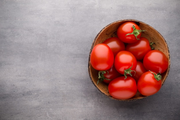 Wiśniowe pomidory w drewnianej misce na szarym tle