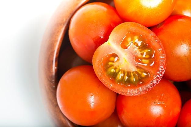 Wiśniowe pomidory w drewnianej misce na tle tekstury tkaniny. widok z góry. fotografia makro