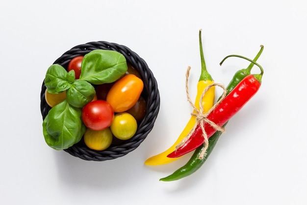 Wiśniowe pomidory w koszu z bazylią i gorącym chili na białym tle. widok z góry świeżych warzyw.