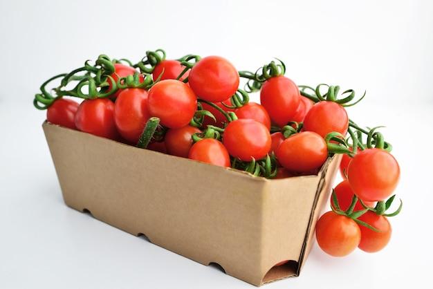Wiśniowe pomidory w papierowym opakowaniu. świeże pomidory czereśniowe w polu na białym tle.