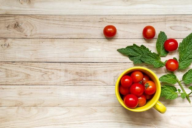 Wiśniowe pomidory w żółtej filiżance i zielonych liściach na jasnym drewnianym stole w tle
