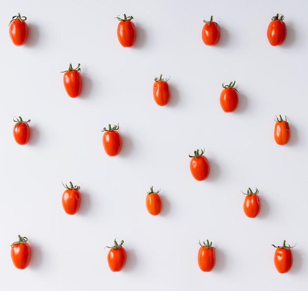 Wiśniowe pomidory wzór na białej ścianie. leżał na płasko.