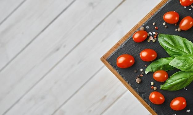 Wiśniowe pomidory z listkami bazylii, solą i pieprzem, układ na czarnej kamiennej desce.