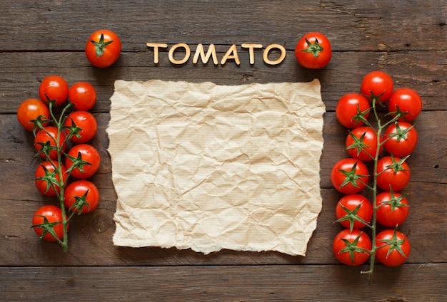 Wiśniowe pomidory z ręcznym papierem i drewnianymi literami na drewnianym widoku z góry