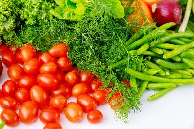 Wiśniowe pomidory, zielony groszek i koper na białym stole.