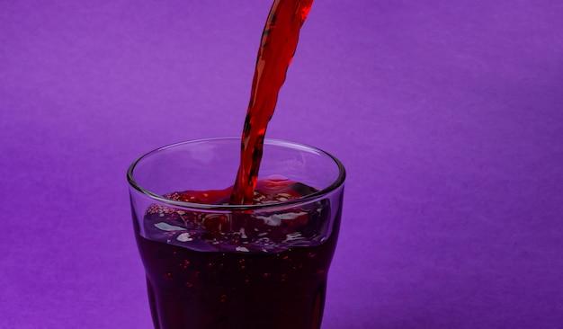 Wiśniowy sok leje do szkła, odizolowane na fioletowym tle