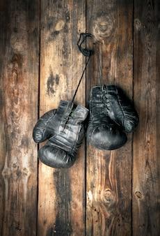 Wiszą bardzo stare skórzane czarne rękawice bokserskie