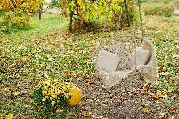 Wisząca huśtawka. jesienne zbiory tarasowe tło. halloween. kraj. dynie i kwiaty. dom wakacyjny. święto dziękczynienia