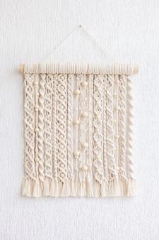Wisząca makrama z drewnianymi koralikami. panel ścienny z bawełnianych nici w kolorze naturalnym. technika makramy do eko wystroju domu i dekoracji ślubnej. nowoczesne zawieszenie ścienne z makramy doda przytulnej atmosfery