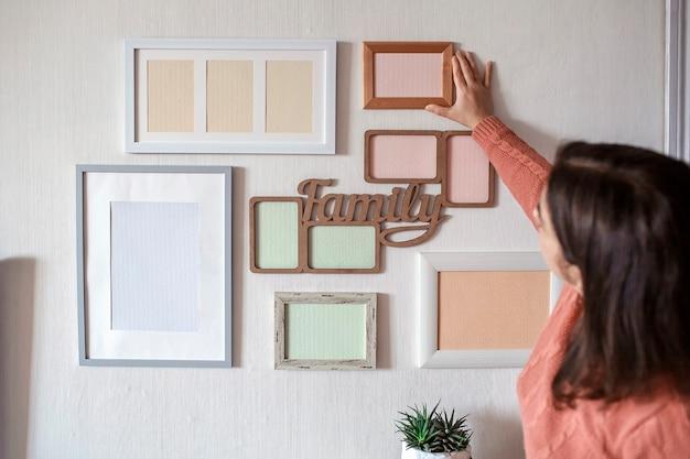Wisząca ramka dziewczyny na białej ścianie z zestawem różnych pustych pionowych i poziomych ramek do zdjęć, aby stworzyć rodzinną galerię zdjęć, uchwycić chwilę, szablon makiety na białej ścianie, styl życia
