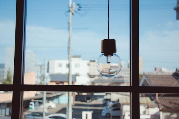 Wisząca żarówka w pobliżu szklanego okna