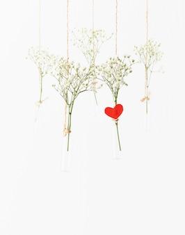 Wiszące białe kwiaty w szklanych mini wazonach. koncepcja walentynki, ślub
