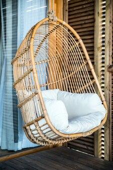 Wiszące krzesło z wikliny z poduszką