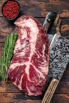 Wiszący delikatny lub wieszakowy stek z surowego mięsa wołowego na desce rzeźniczej z tasakiem