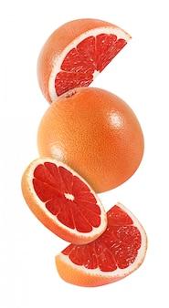 Wiszący, spadający i latający kawałek grapefruitowe owoc odizolowywać na białym tle z ścinek ścieżką