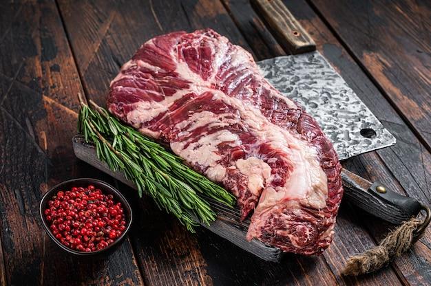 Wiszący stek z polędwicy lub wieszaka z surowego mięsa wołowego na desce rzeźniczej z tasakiem. ciemne drewniane tło. widok z góry.
