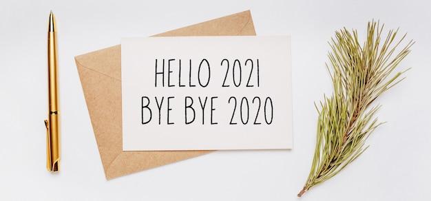 Witaj 2021 pa pa pa 2020 notatka z kopertą, gałązką świerku i złotym długopisem na białej powierzchni. wesołych świąt i nowego roku koncepcja