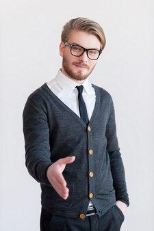 Witaj na pokładzie! przystojny młody mężczyzna w okularach wyciągający rękę do potrząsania stojąc na szarym tle