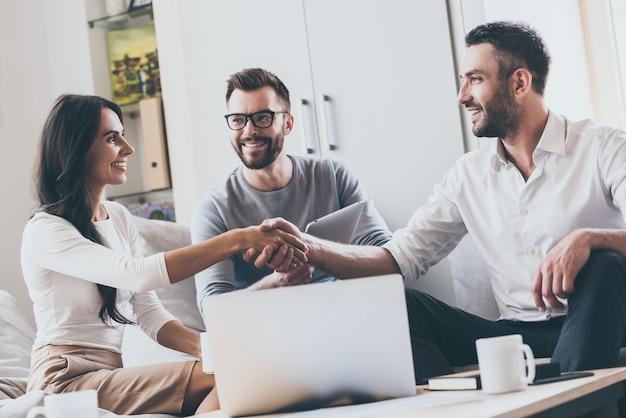 Witaj na pokładzie! trzech młodych, wesołych ludzi biznesu siedzących razem przy biurku, podczas gdy mężczyzna i kobieta podają sobie ręce